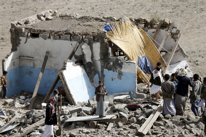 People gather on wreckage of house destroyed by air strike in Bait Rejal village west of Yemen' class=