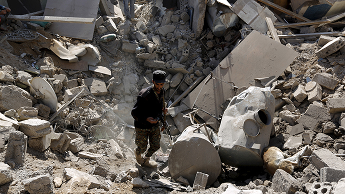 A police trooper walks in a creater caused by an air strike on houses near Sanaa Airport March 31, 2015 (Reuters / Khaled Abdullah)