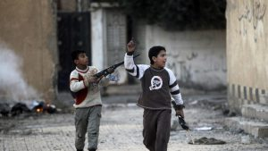 Children play with their toy weapons in a damaged school in Deir al-Zor, eastern Syria February 21, 2014. Picture taken February 21, 2014. REUTERS/Khalil Ashawi (SYRIA - Tags: POLITICS CIVIL UNREST CONFLICT) - RTX19ARC